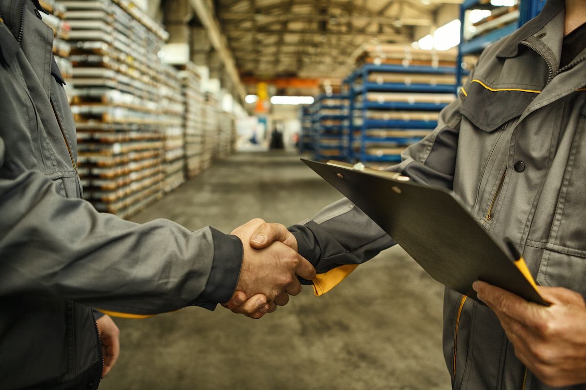 Cropped close up of a worker holding clipboard shaking hands with his colleague at the industrial storage copyspace teamwork partnership metalworking hardware industry